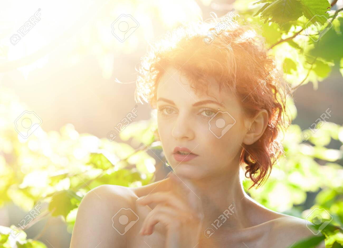 Portrait of a young red-haired woman among the foliage of trees illuminated by the suns rays - 155881142