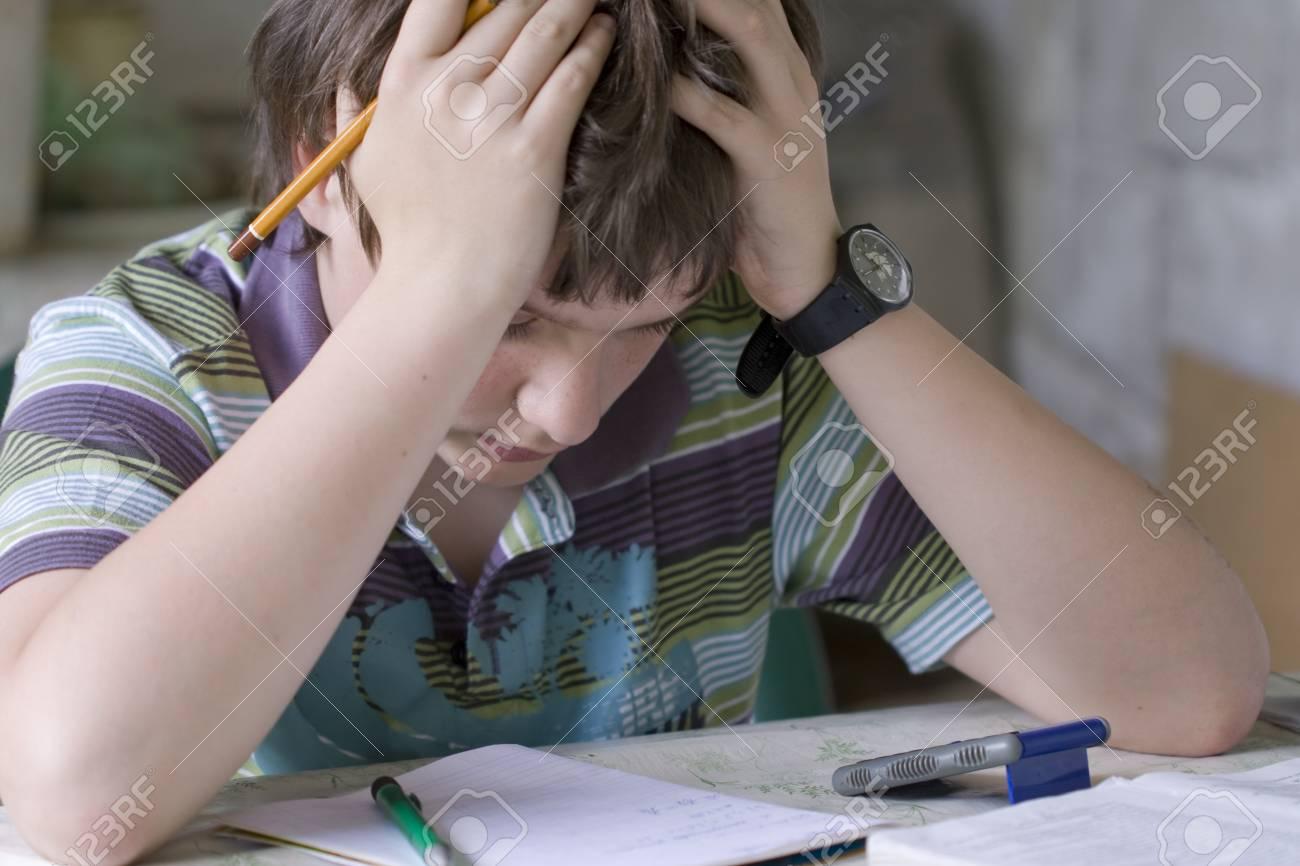 Thinking boy hardly solving homework Stock Photo - 11089355