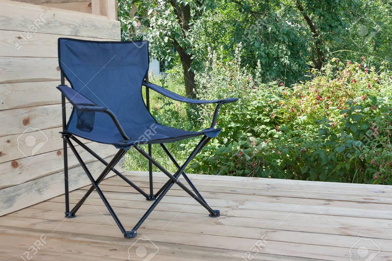 Chaise pliante pour se reposer dans le jardin d'été près de buissons de framboises mûres, gros plan