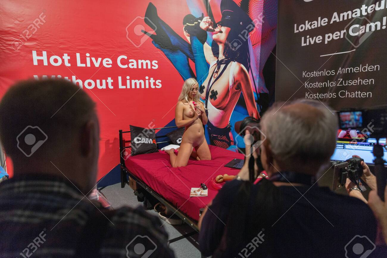 BERLIN, GERMANY - OCTOBER 17, 2019: People visit Hot Live Cams online amateur booth at Venus trade fair with trends and innovations from the and lifestyle in Messe exhibition hall. - 137376471