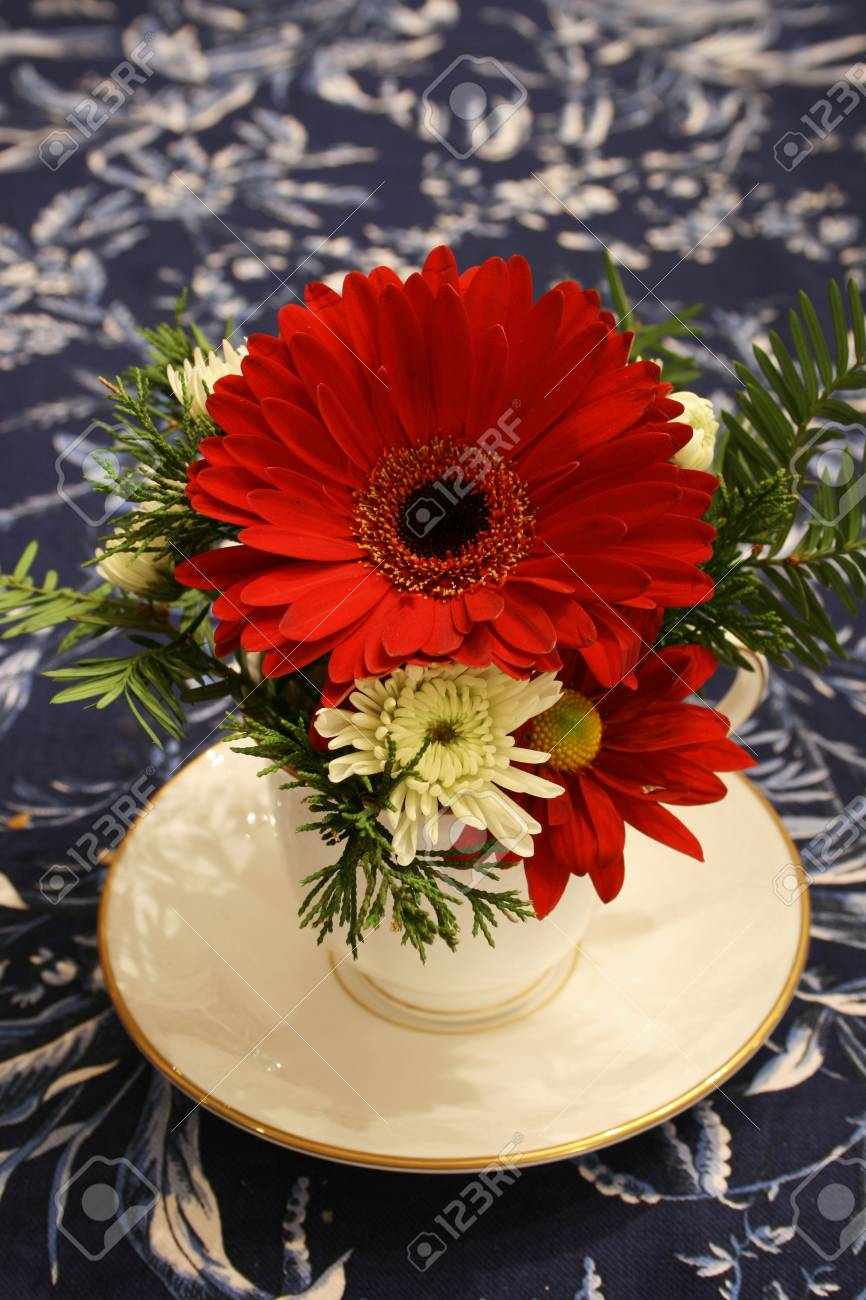 vertical image of red and white flowers in a cup as a centerpiece on a blue floral tablecloth Stock Photo - 3659483