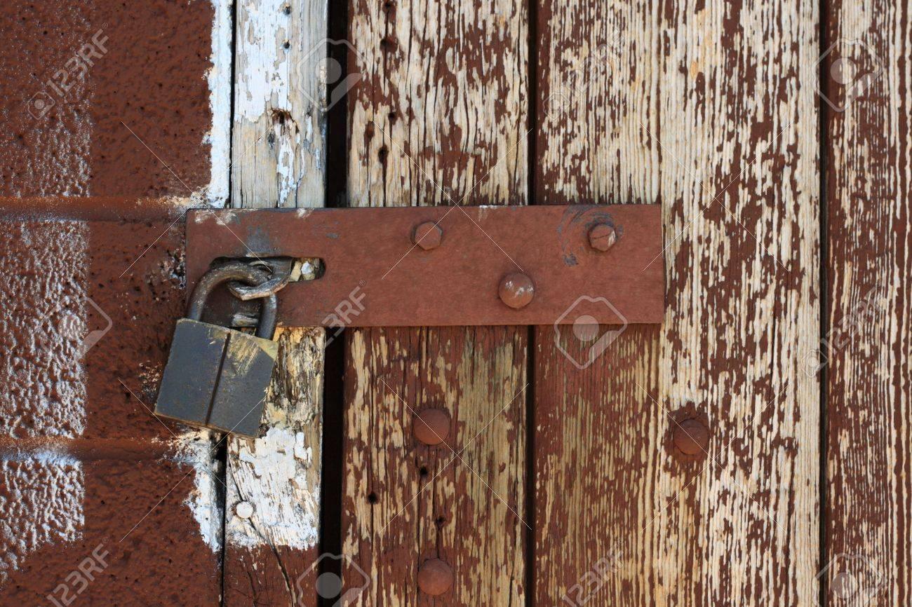Stock Photo - padlocked hasp on weathered painted brown wood door & Padlocked Hasp On Weathered Painted Brown Wood Door Stock Photo ... Pezcame.Com