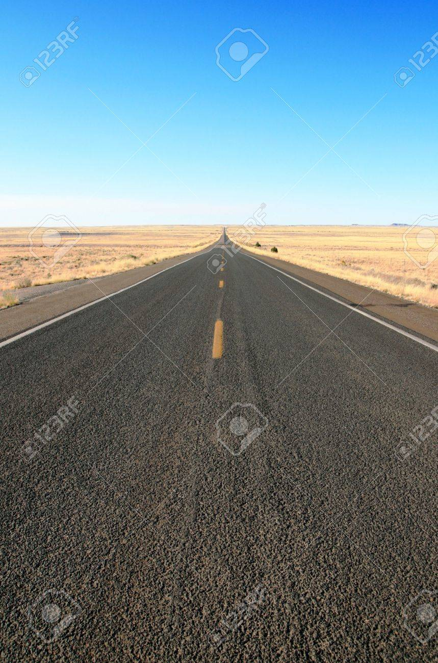 highway 180 in Northern Arizona cuts straight across the grasslands to the horizon under a blue sky Stock Photo - 3825278