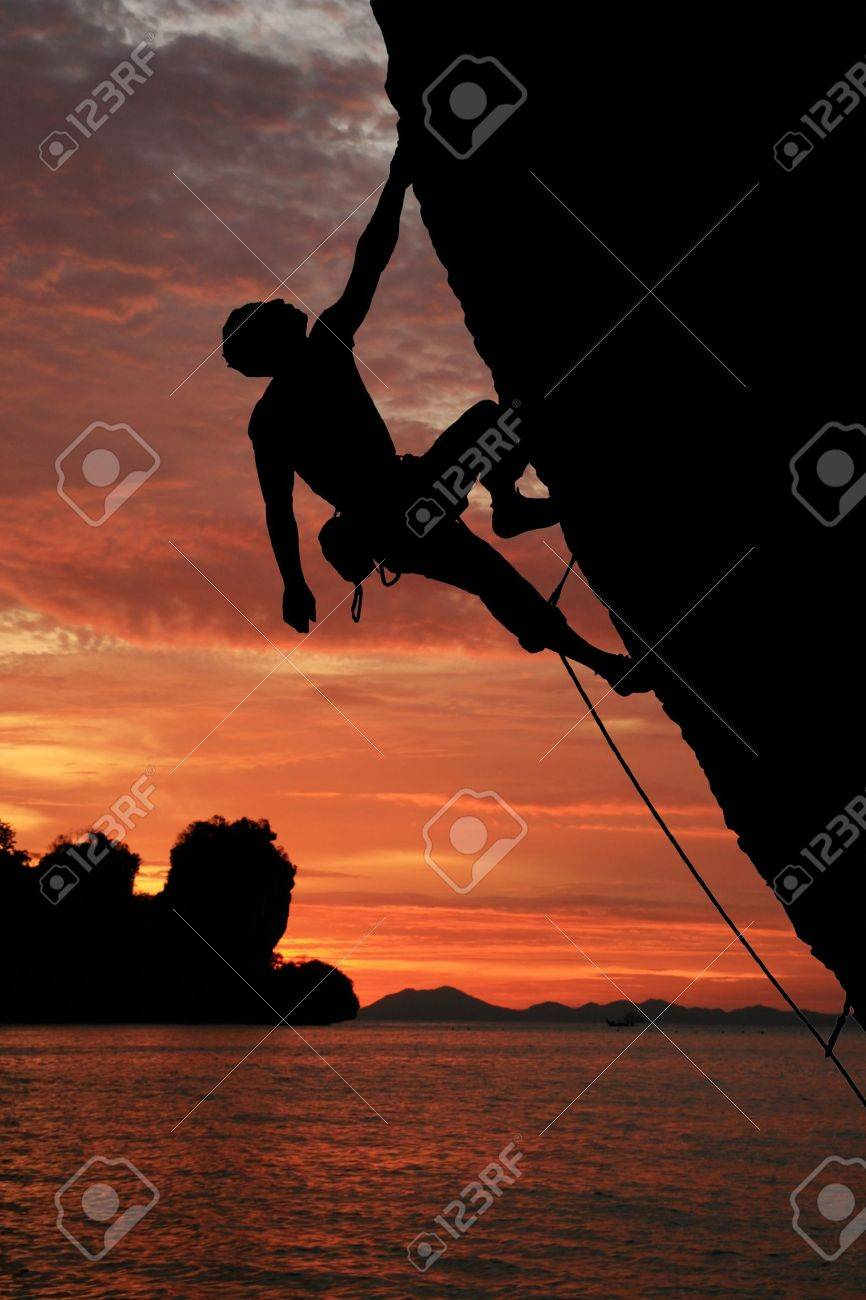 silhouette of rock climber climbing an overhanging cliff with sunset over the ocean background Stock Photo - 6659811