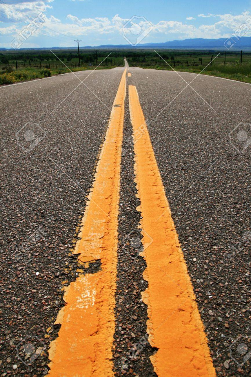 yellow lines on a rural road heading into the distance Stock Photo - 6988303