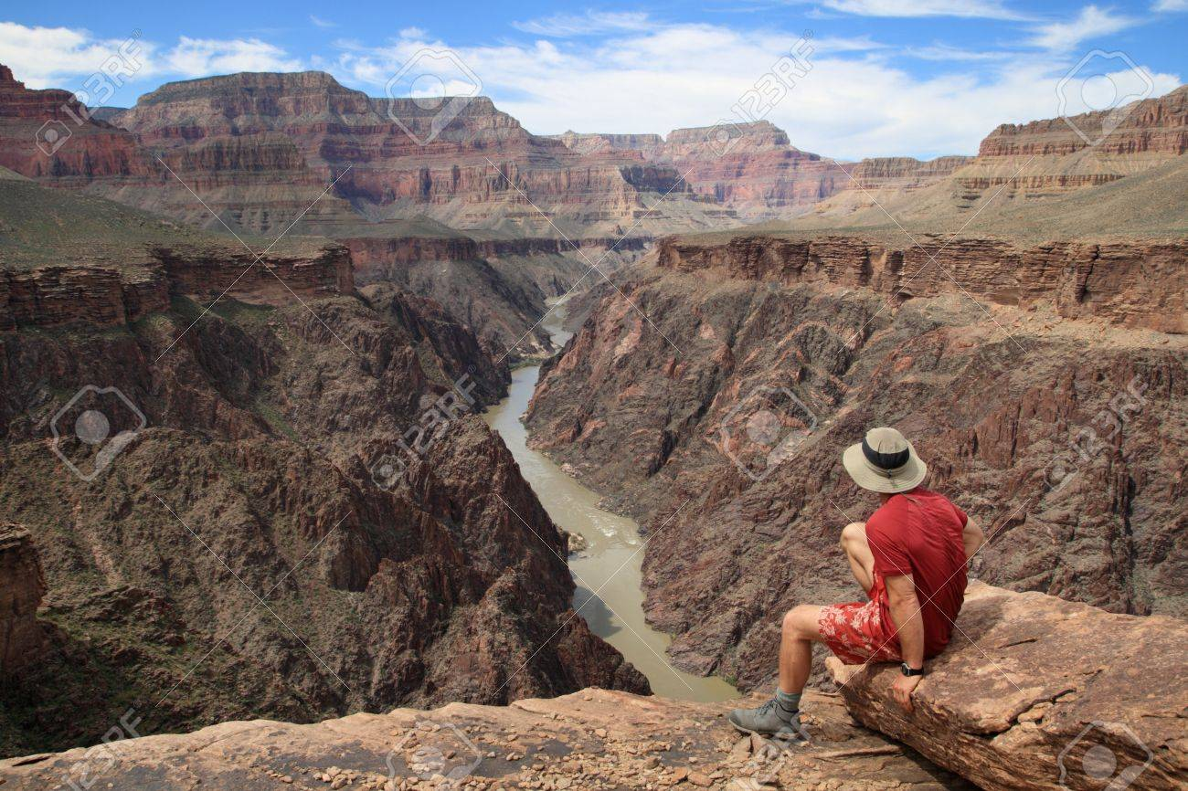 a man sitting on an overlook in the Grand Canyon looking down into Granite Gorge from the Tonto Plateau Stock Photo - 9272971