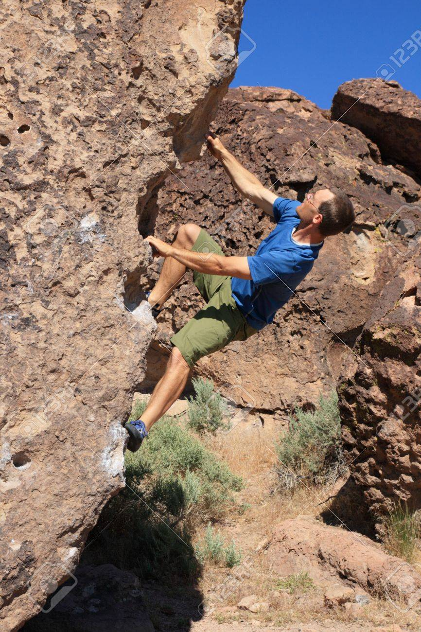 a man in a blue shirt bouldering on volcanic tuff rock Stock Photo - 9771498