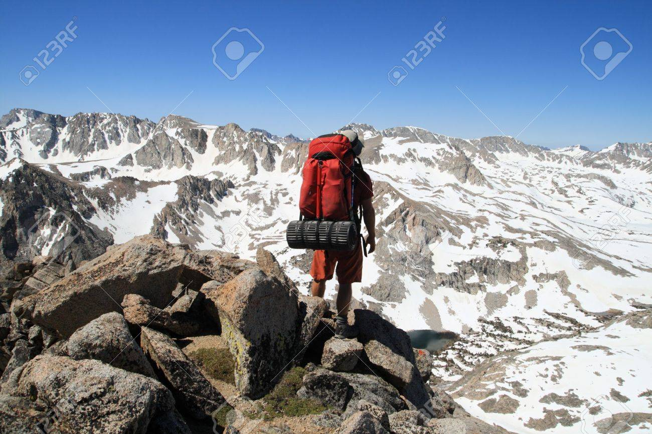 back view of a male backpacker looking down on Piute Pass in the Sierra Nevada Mountains from Mount Emerson Stock Photo - 9883989