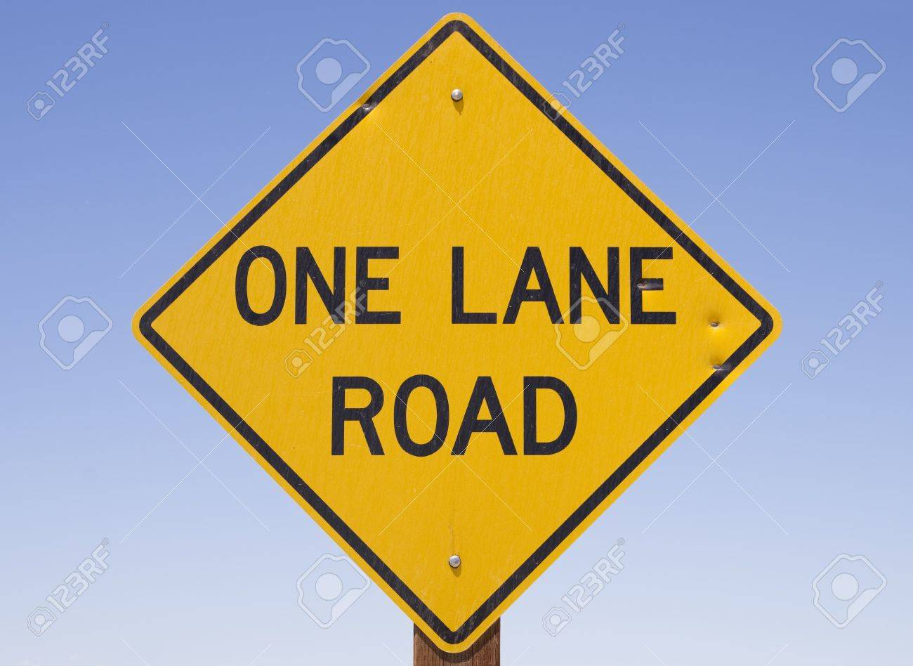 yellow and black one lane road sign with blue sky background Stock Photo - 14459416