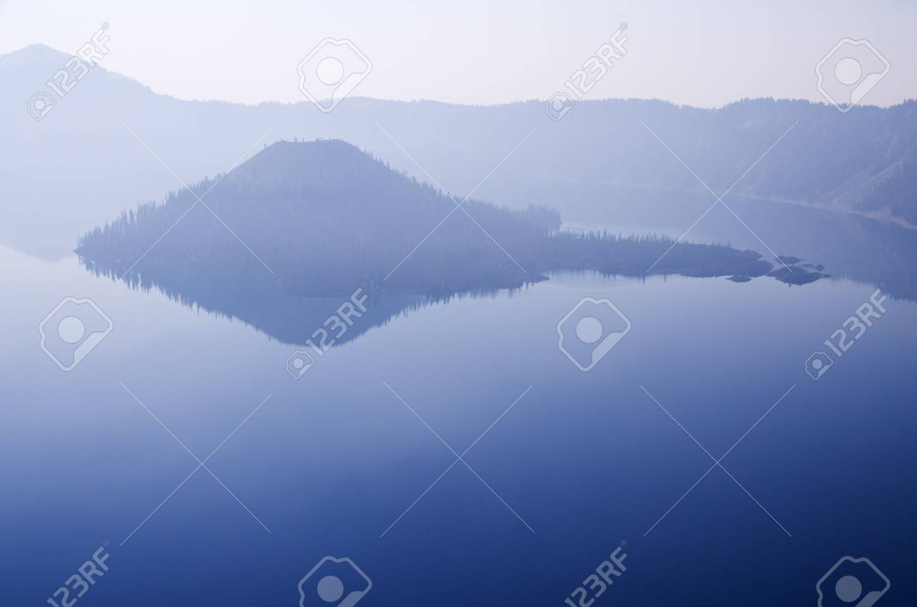 Wizard Island in Crater Lake on a hazy day with reflections and copy space Stock Photo - 15608419