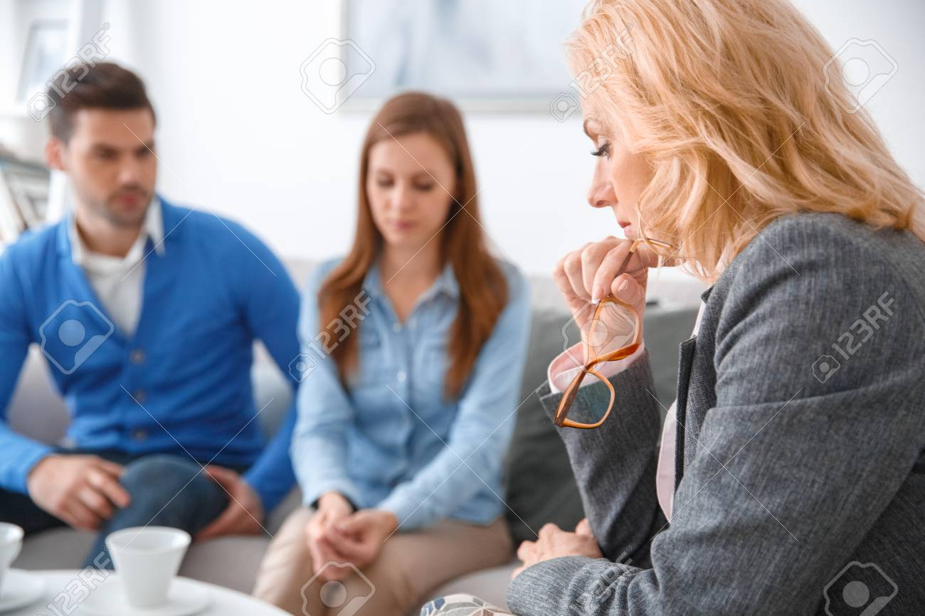 Young couple with psychologist family therapy therapist looking