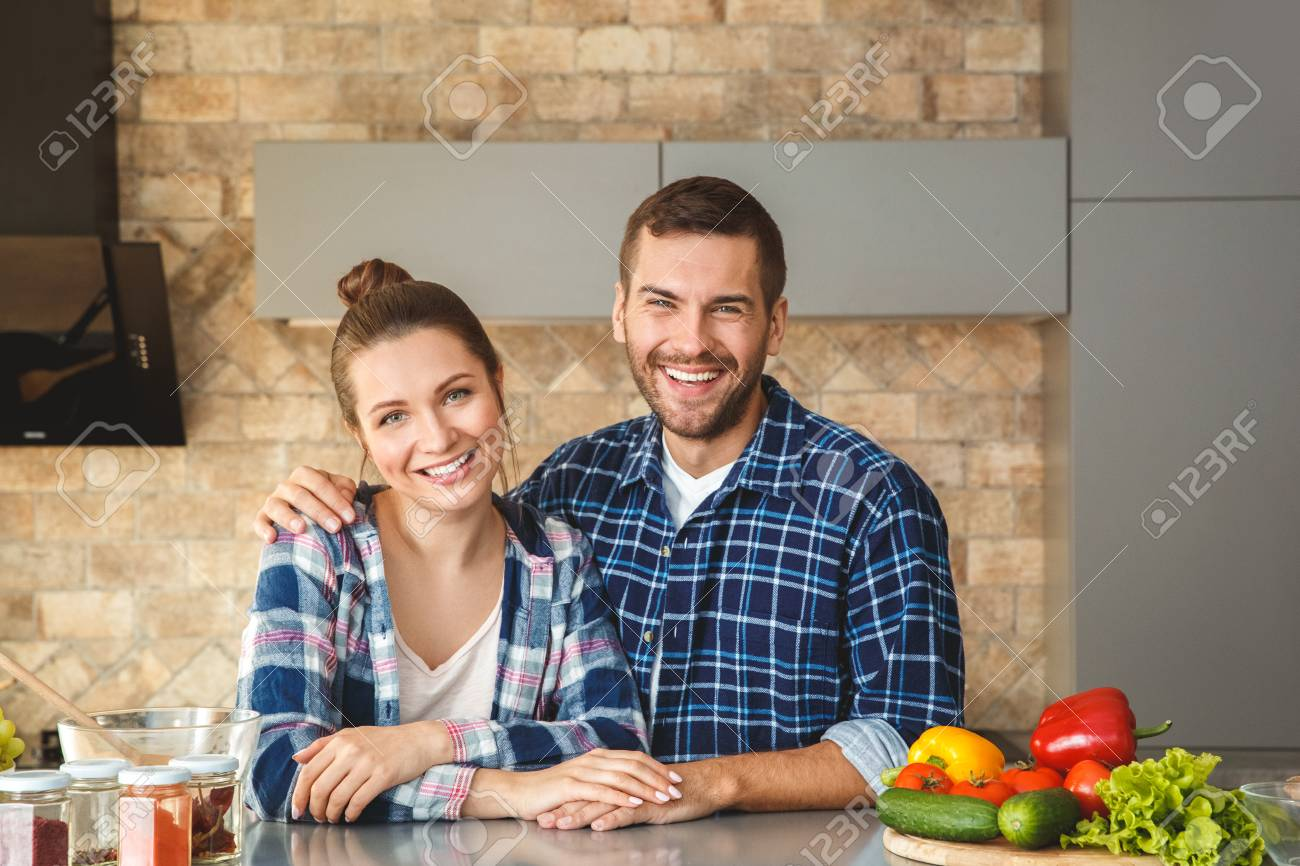 Young Couple At Home Standleaning On Table Ing In Kitchen Together
