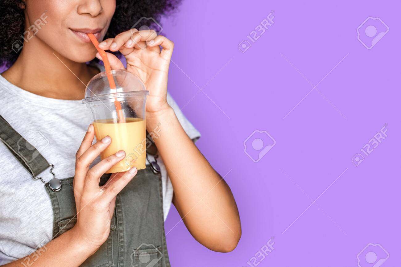 Freestyle. African american girl wearing denim overall standing isolated on blue drinking smoothie joyful close-up - 142426416