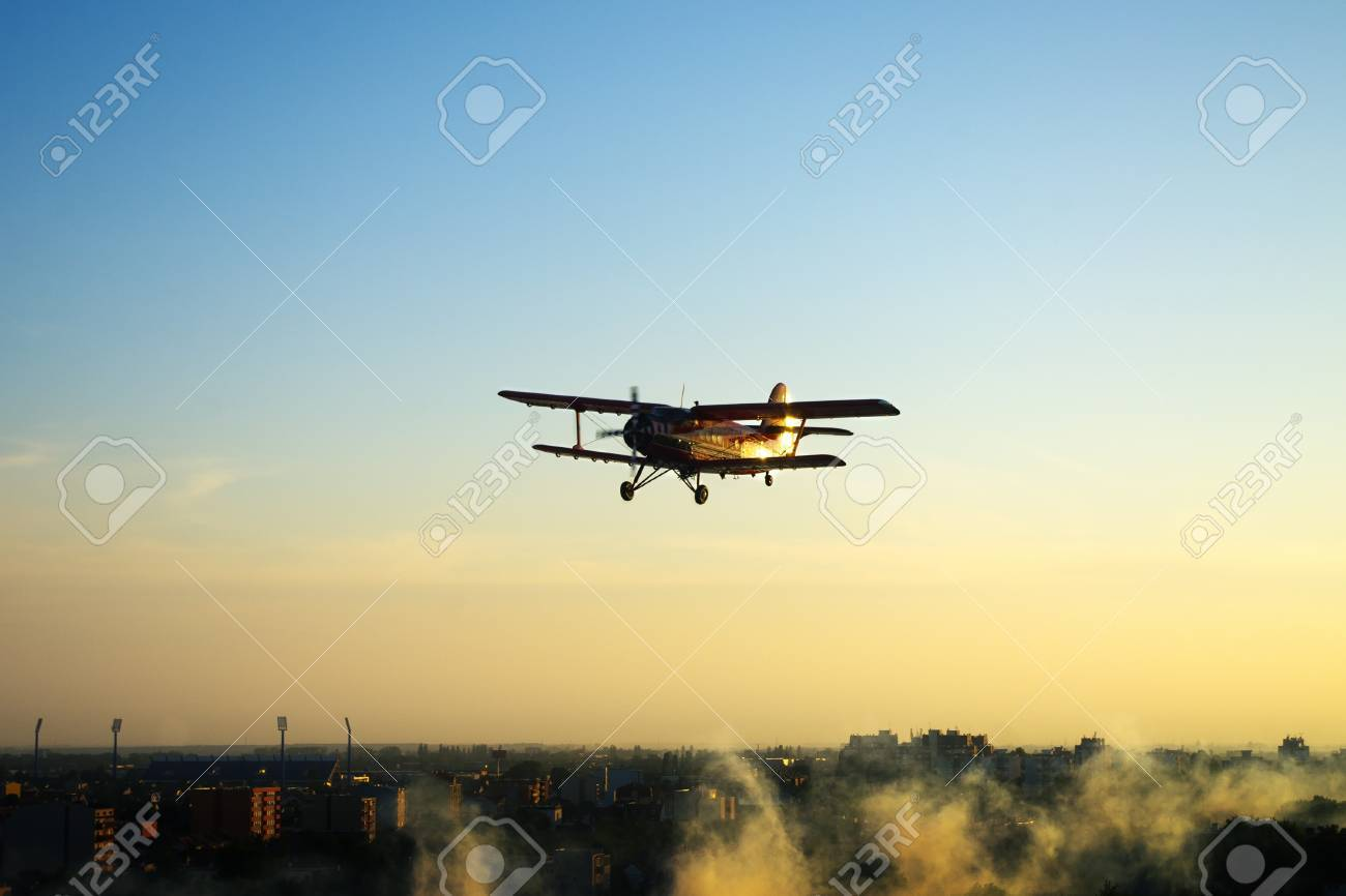 Silhouette of vintage red airplane flying over town Stock Photo - 20174985