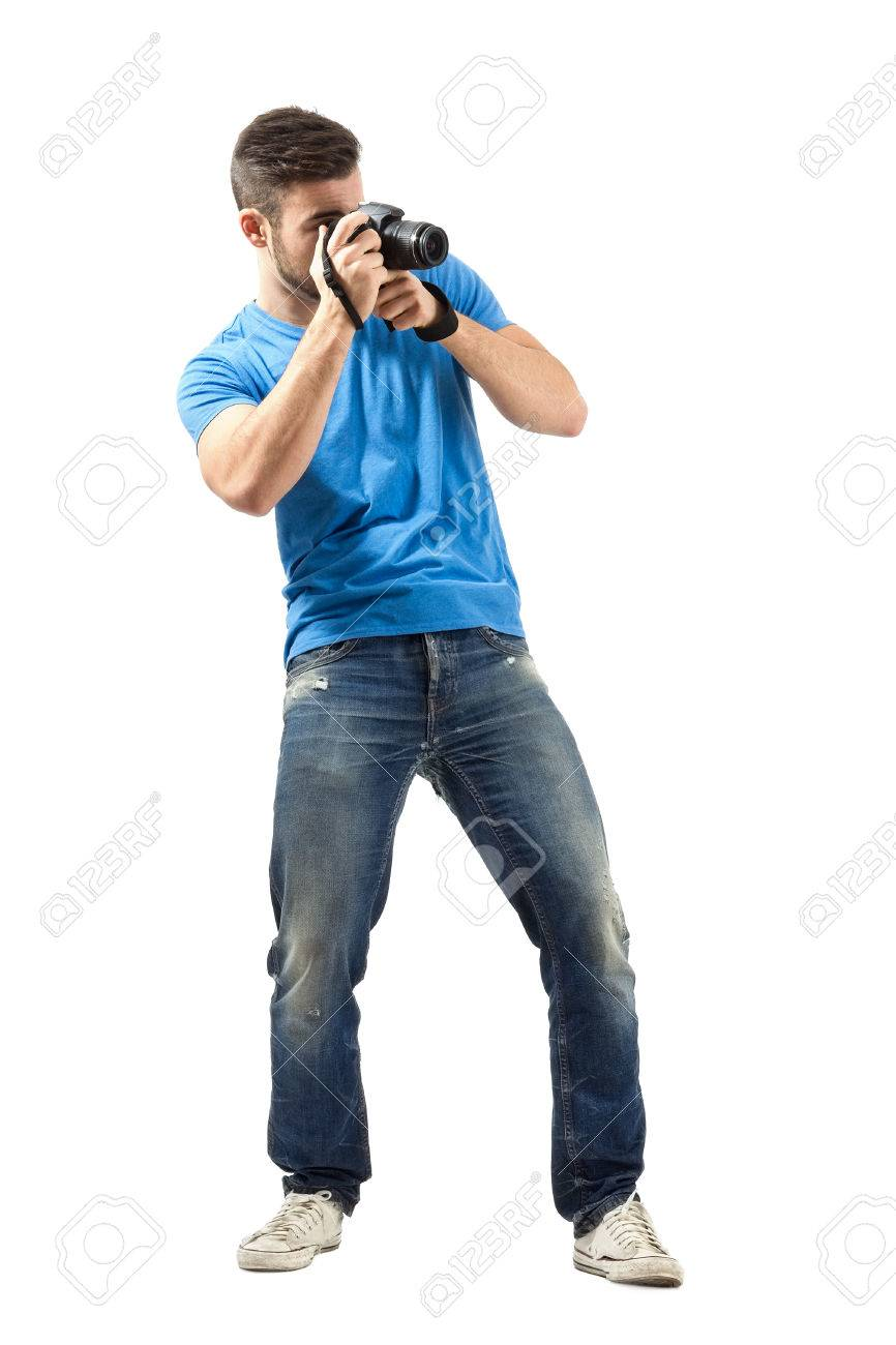 Standing young man taking photo with dslr  Full body length portrait