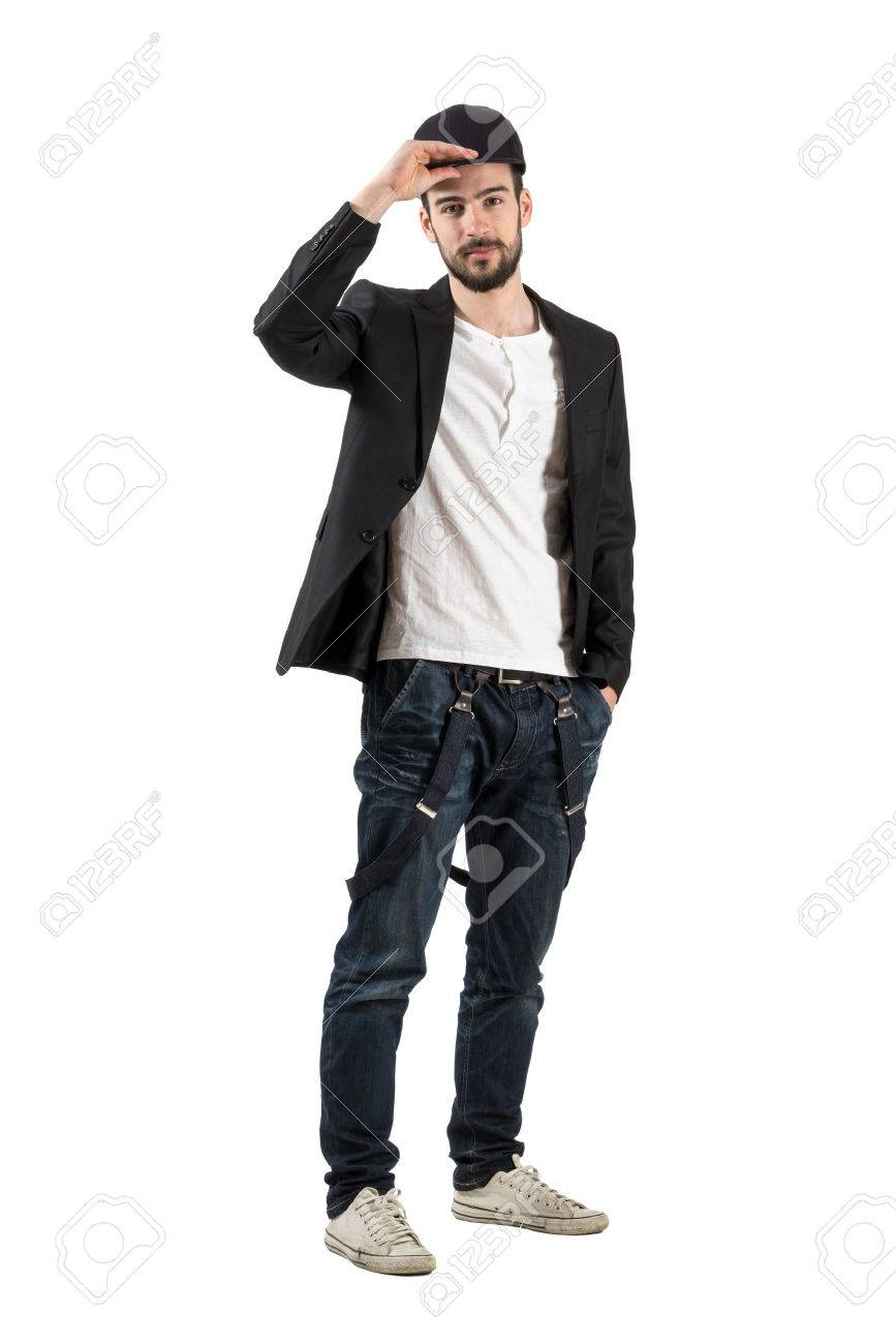 f6305ee82ef Banque d images - Jeune homme à la mode maintenant mettre casquette de  baseball sur la tête. Corps pleine longueur portrait isolé sur fond blanc.