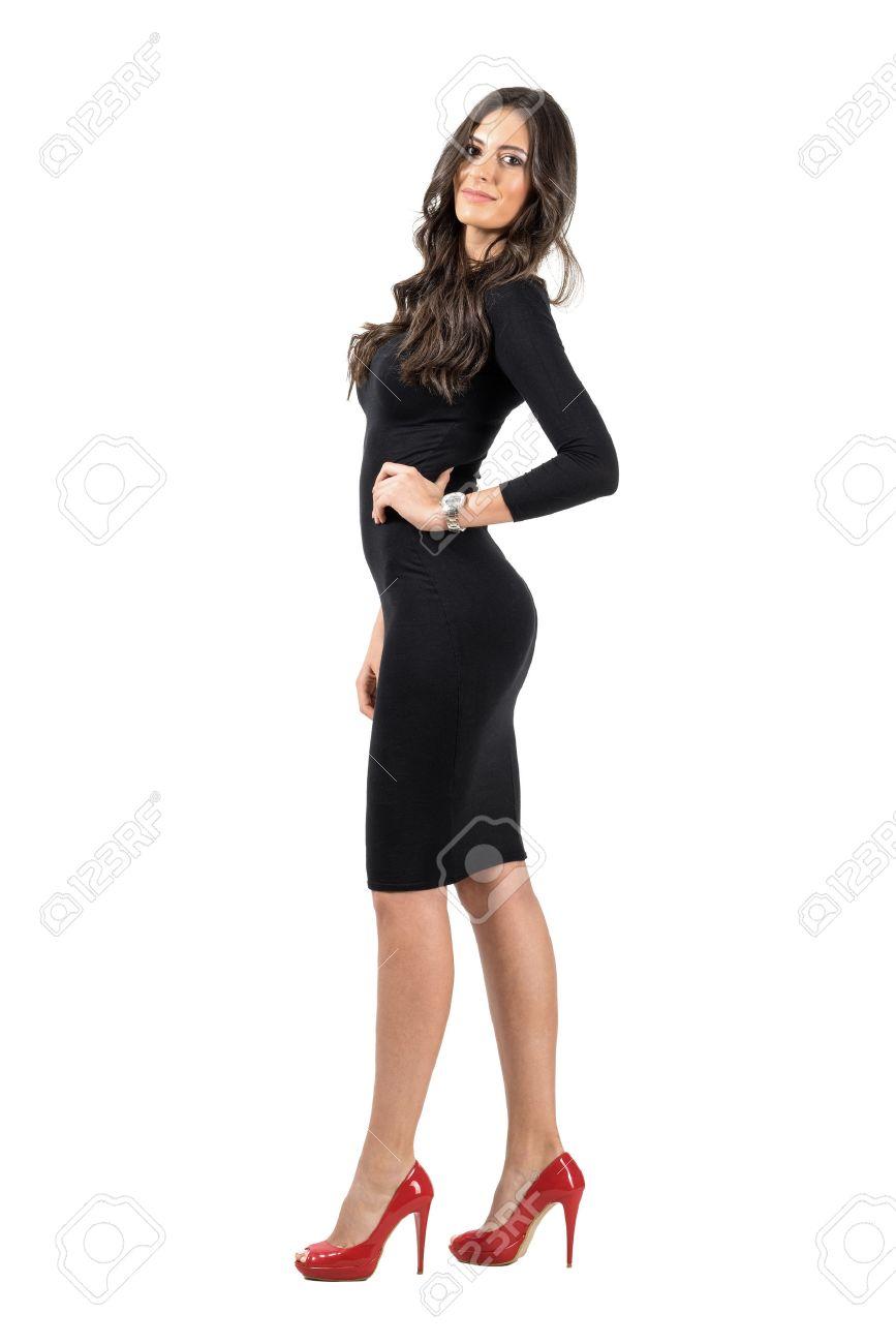 Joven Mujer De Negocios Latinos En Vestido Negro Corto Posando A La Cámara Retrato De Cuerpo Entero Aislado Sobre Fondo Blanco De Estudio
