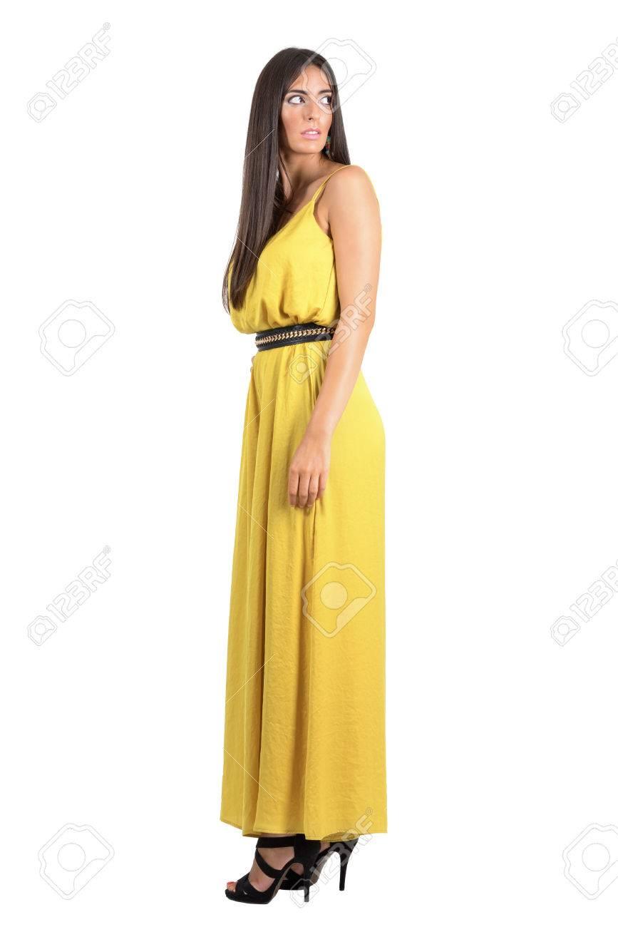 16006e3f2b Foto de archivo - Vista lateral del modelo de manera miedo en vestido de noche  amarillo mirando hacia atrás por encima del hombro. la longitud del cuerpo  ...