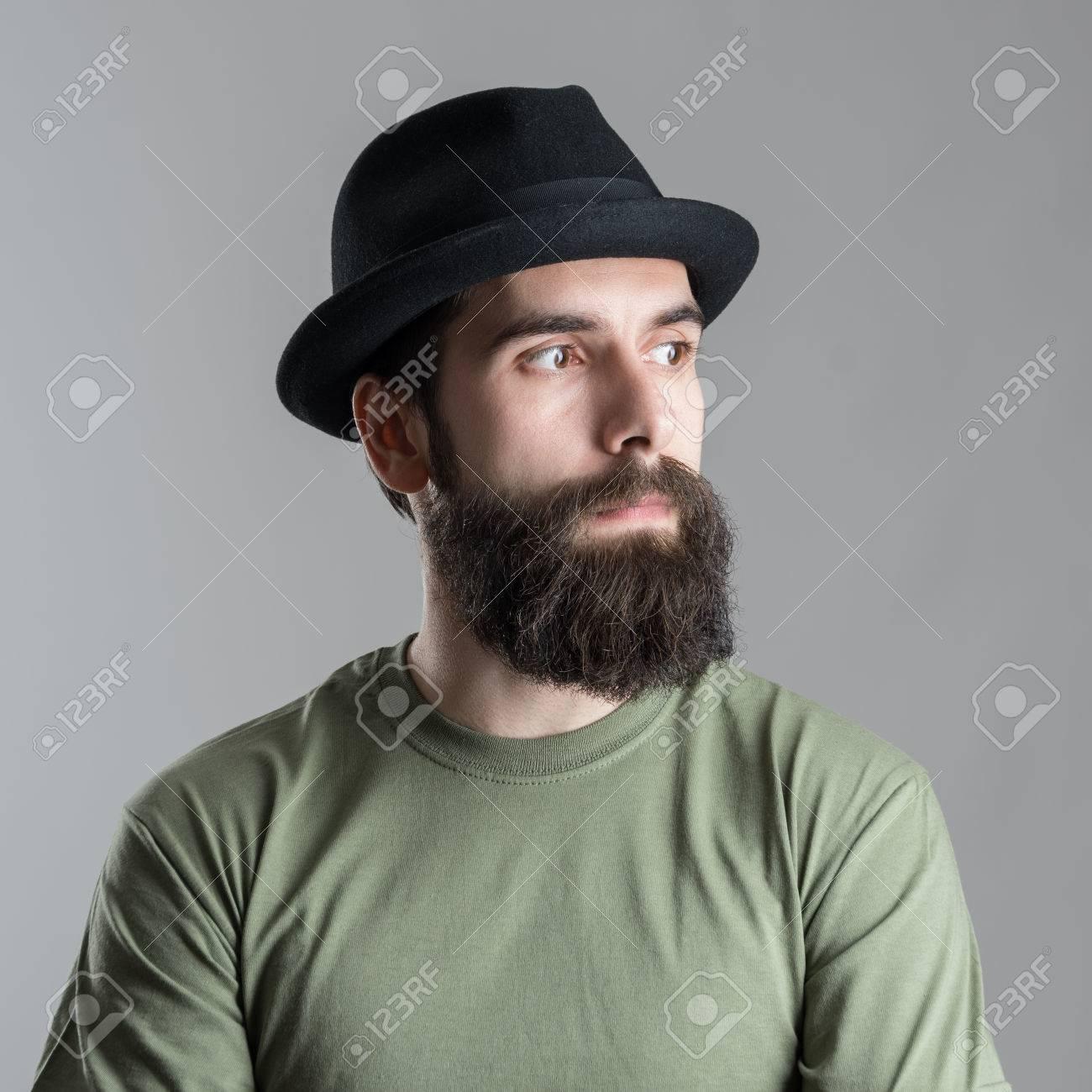 de2d5bf9fc Grave uomo con la barba pensieroso guardando altrove. Primo piano del volto  vicino ritratto su sfondo grigio studio.