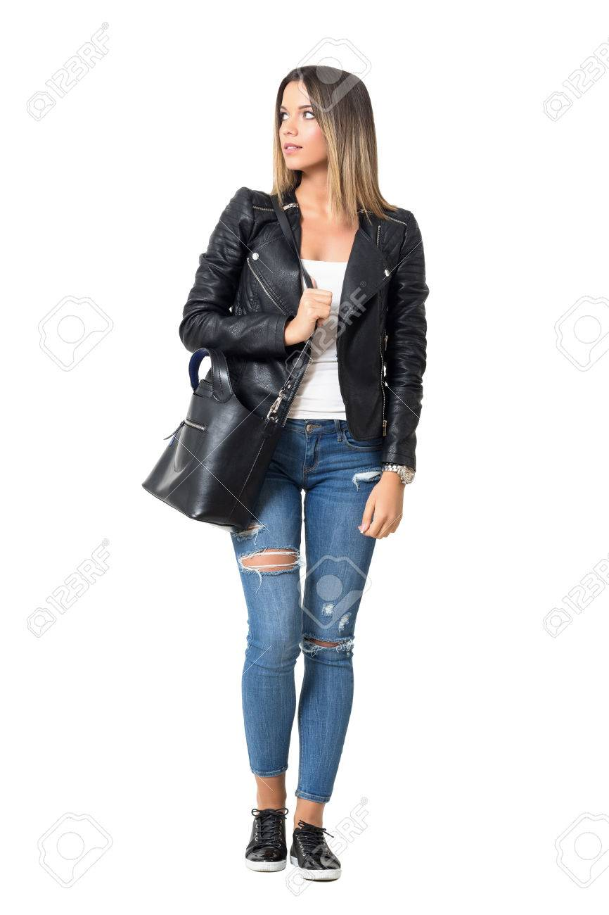 c37170ef8d4da Stock Photo - Street style fashion model carrying bag walking and looking  away. Full body length portrait isolated over white background