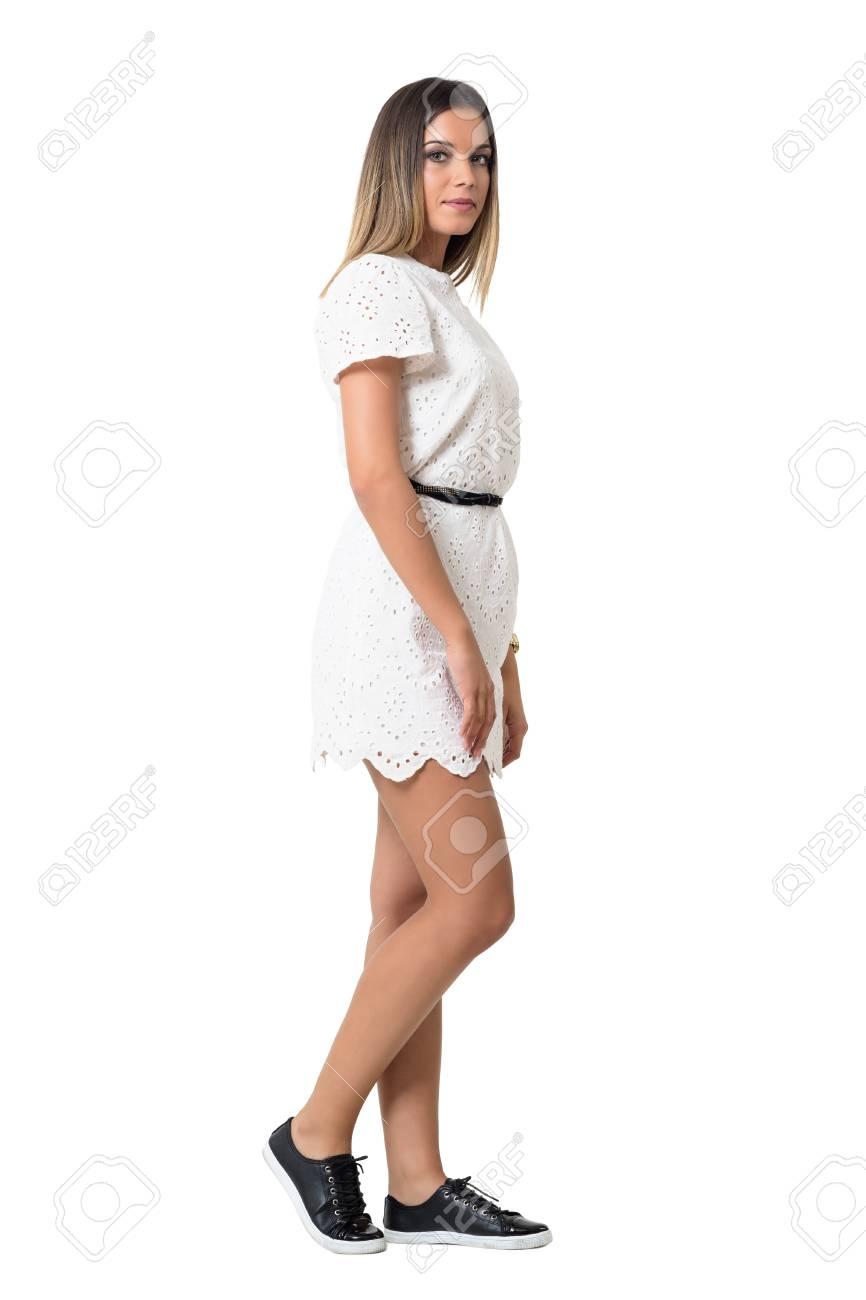 ce2ac80dec Foto de archivo - Vista lateral de la mujer con estilo joven en vestido  blanco caminando y mirando a la cámara. la longitud del cuerpo Retrato  completo ...