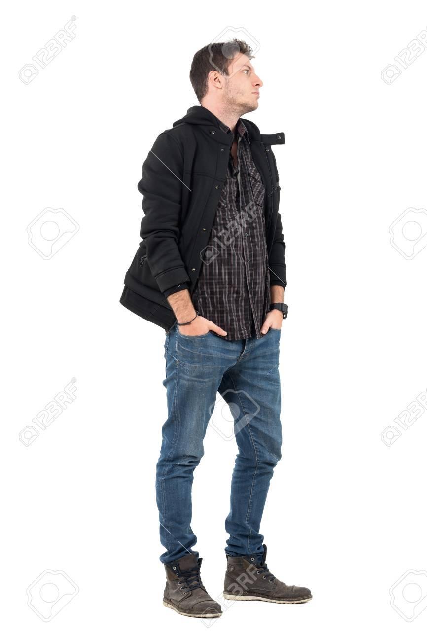 e90e52b6779a6 Foto de archivo - Vista lateral del hombre joven en ropa de otoño con las  manos en los bolsillos mirando de lejos. Retrato de cuerpo entero sobre  fondo ...