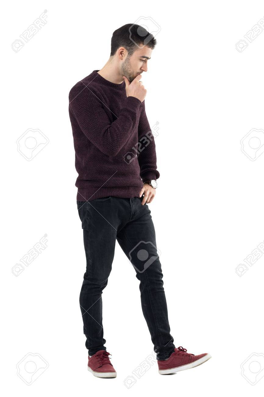 fc3b0d7c13 Stock Photo - Thoughtful stressed casual man walking and looking down. Full  body length portrait isolated over white studio background.
