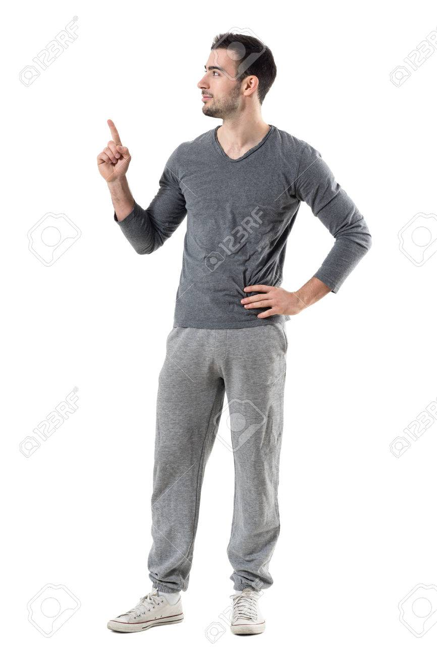 Fit Sport Man In Sweat Pants And Gray Shirt Pointing Finger Up