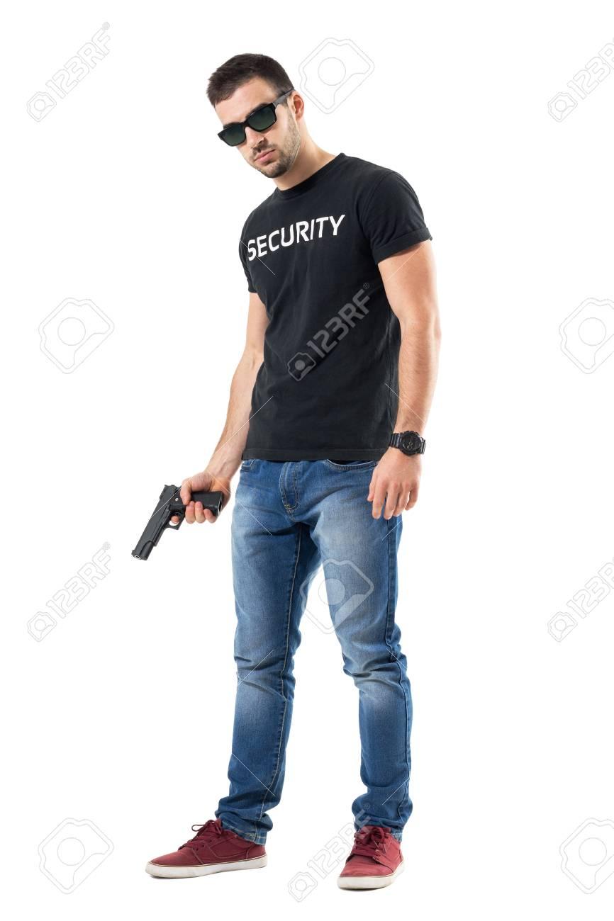 Agent de vêtements plaine confiant robuste avec des lunettes de soleil  tenant le pistolet en regardant 985d875c0bce