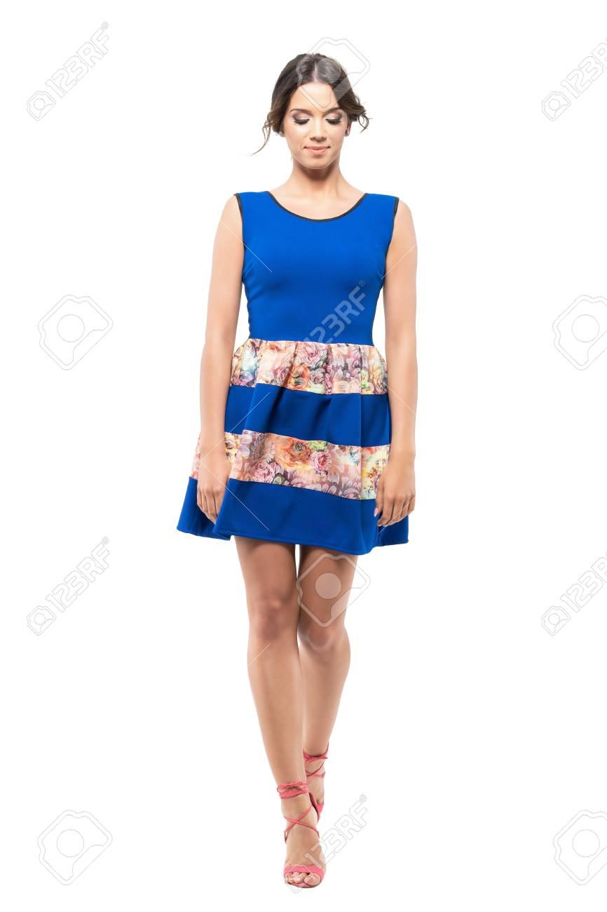 77660e857 Foto de archivo - Linda mujer linda licitación en vestido de verano azul  caminando y mirando hacia abajo. Retrato de longitud completa del cuerpo  aislado en ...