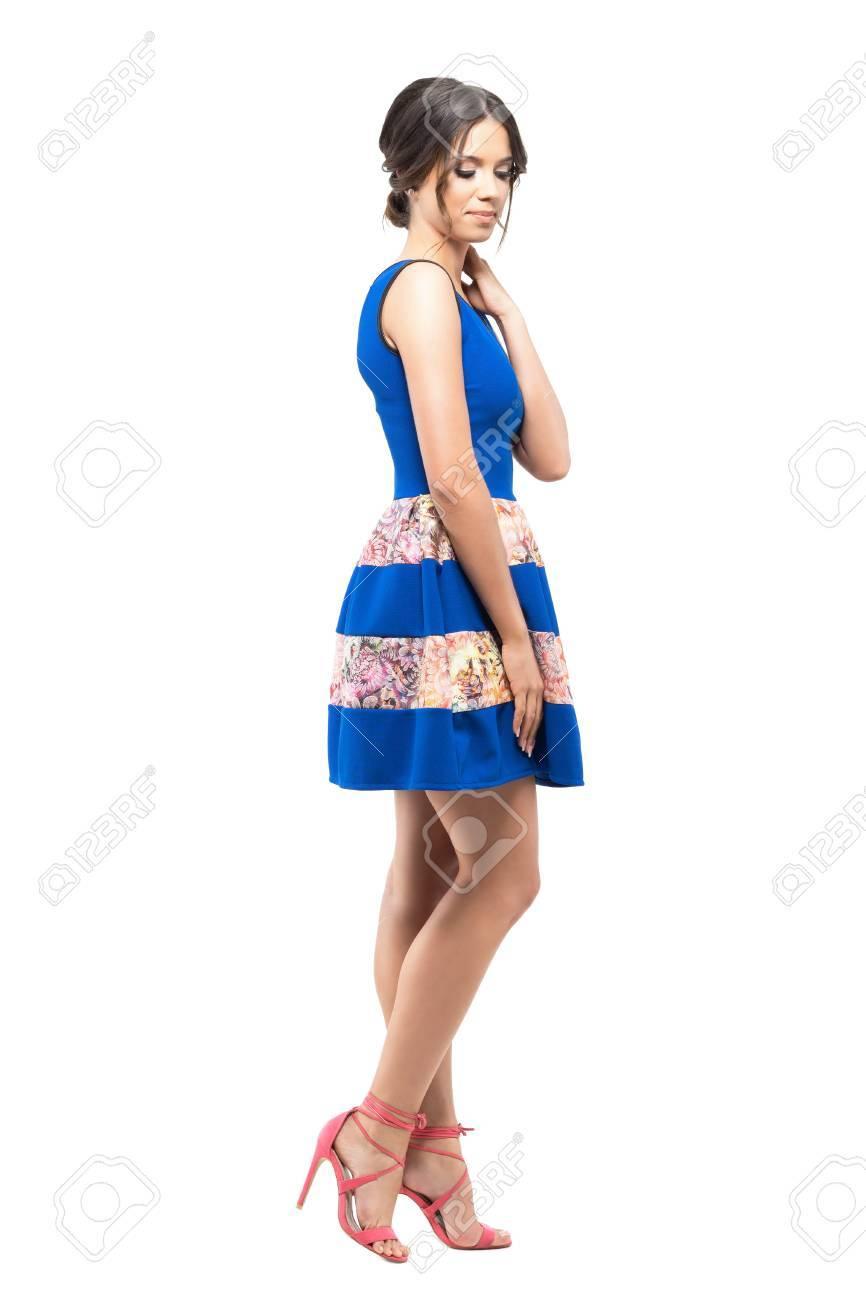 77750b3a7d22 ... isolato su sfondo bianco studio. Giovane donna alla moda tenera in  vestito senza maniche da estate corta blu che guarda giù