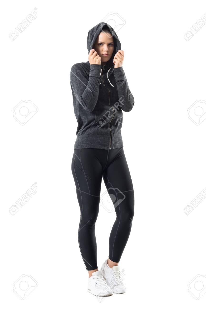 c88a95b9183e6 Deportiva mujer en ropa deportiva de otoño cálido con capucha en la cabeza  mirando a la