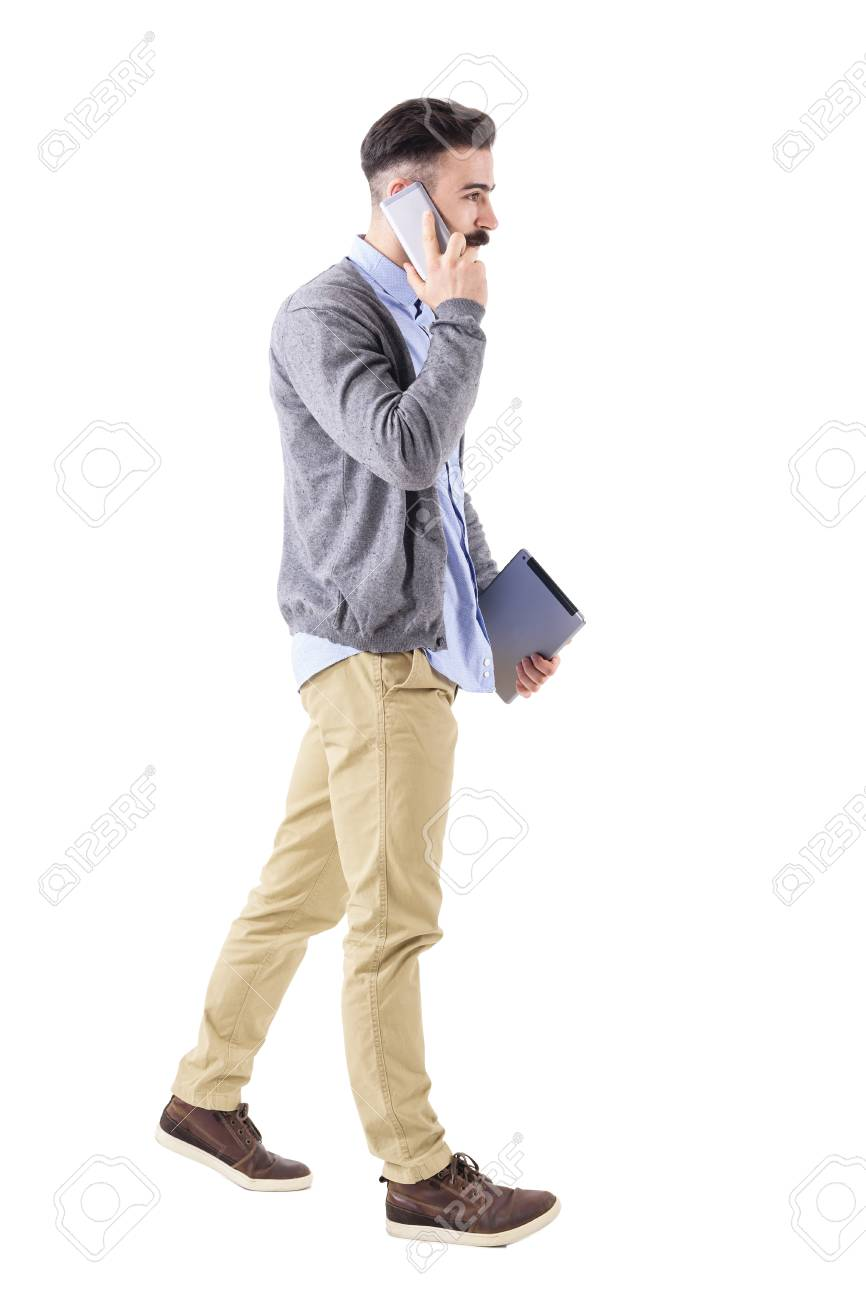 213226e07a3d Confident young businessman with tablet on the phone, walk and look away.  Full body