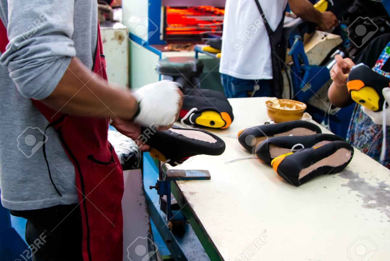 5dfa7a54a8 Foto de archivo - Trabajador de artesanía haciendo zapatos en línea de  producción de calzado