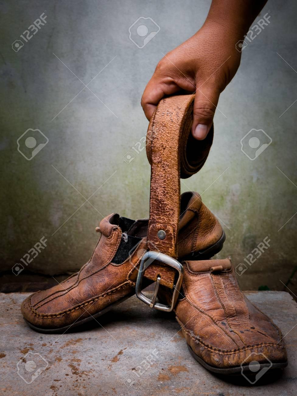 prezzo all'ingrosso prezzo moderato varietà di design Tenere in mano vecchie scarpe di pelle e cintura. È più di pelle sporca e  squallida. È ora di cambiare scarpe nuove o ripararle.
