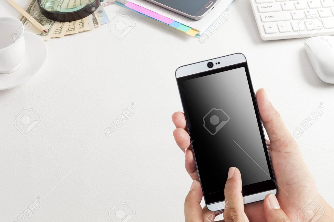 Utilisation à la main smartphone avec table de bureau de bureau