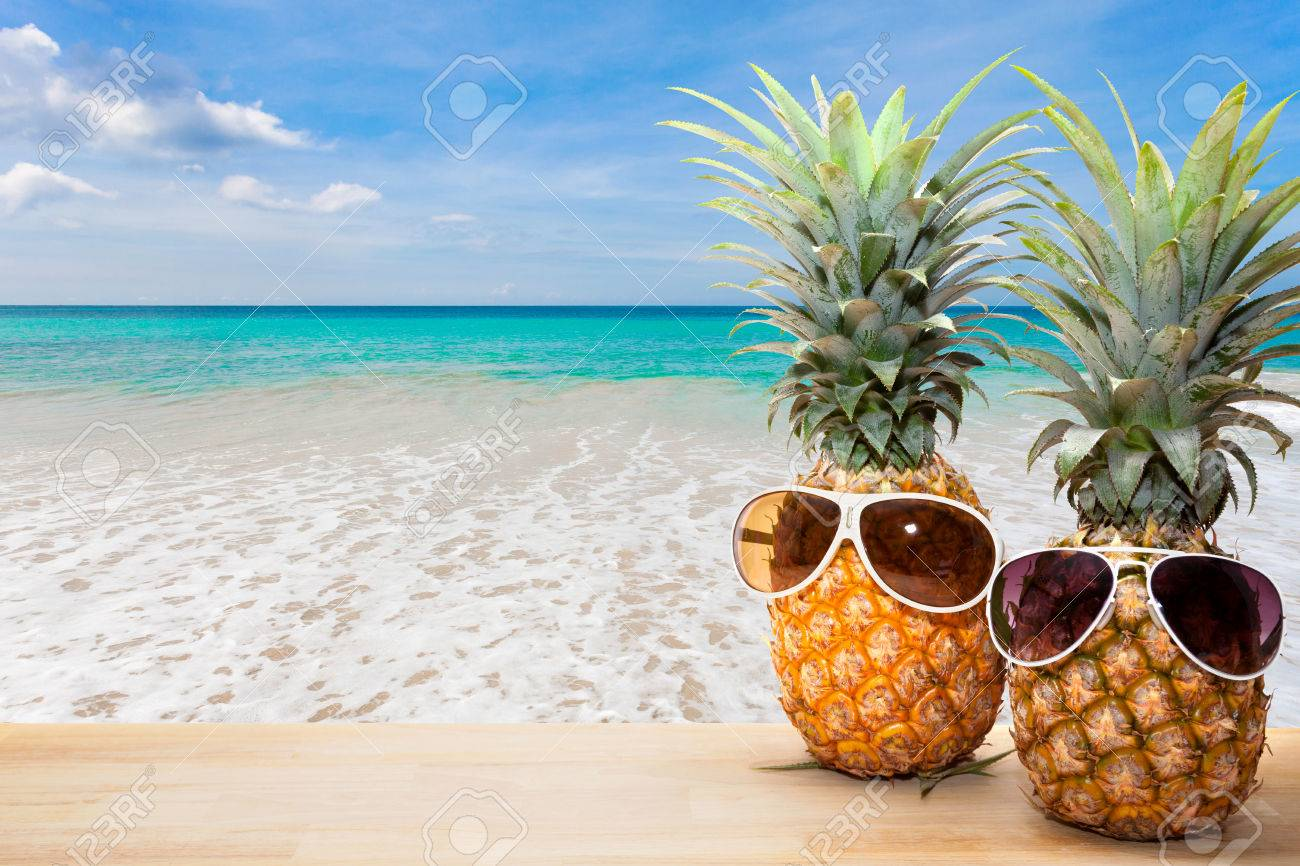 pineapple with sunglasses on beach background concept summer stock