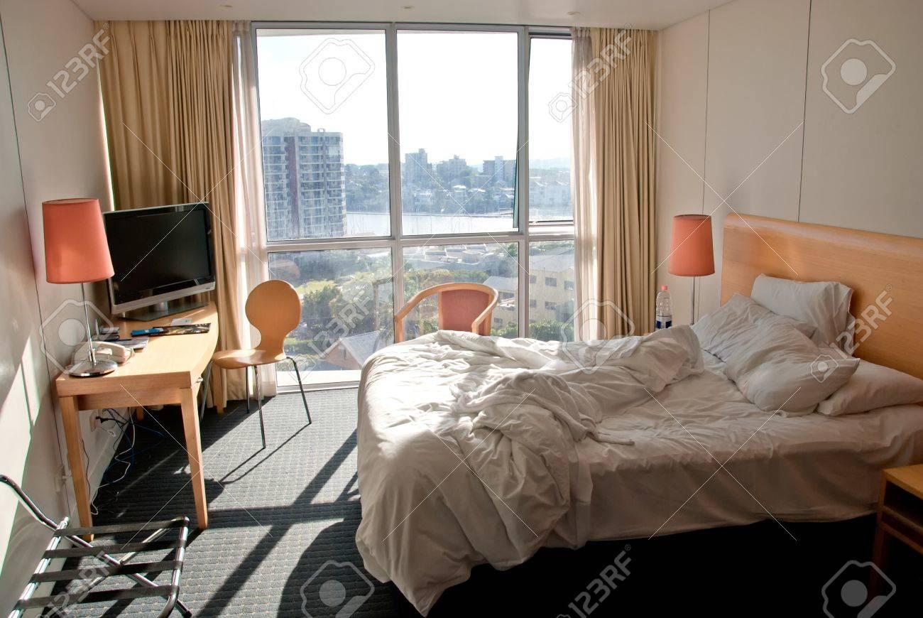 hotel slaapkamer met onopgemaakt bed en uitzicht op de stad australi stockfoto 20020467