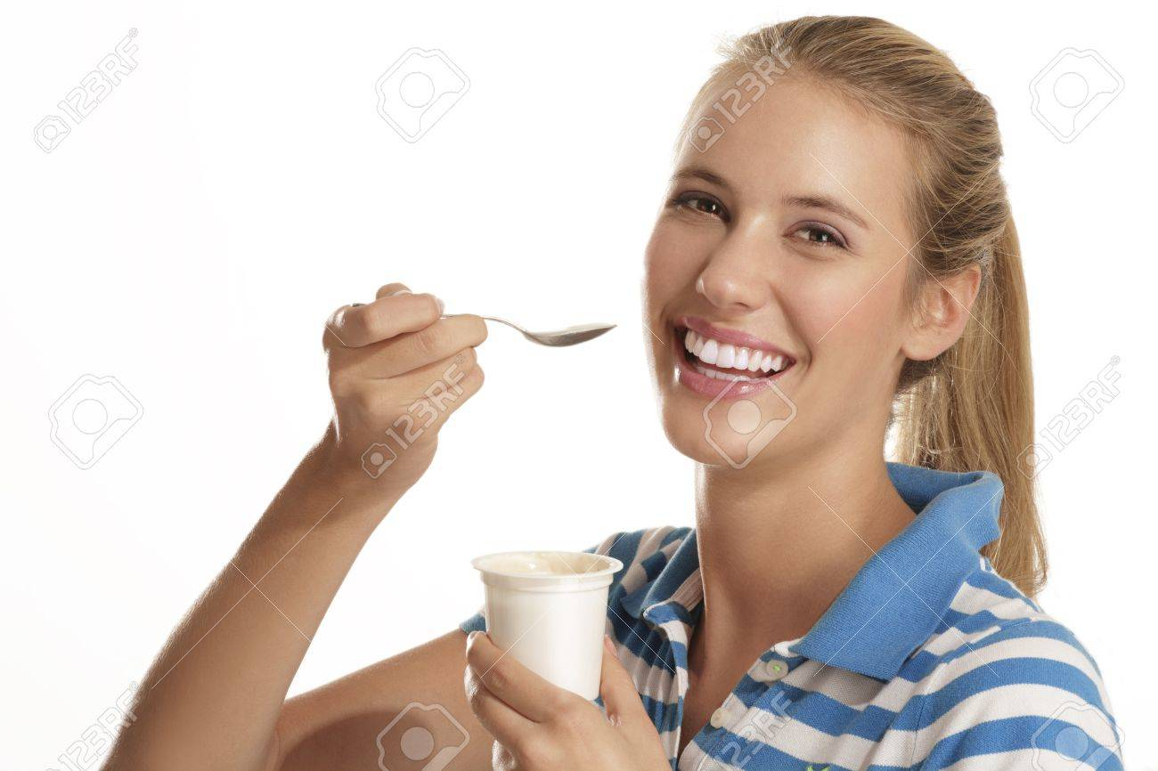 young woman eating yogurt on white background - 15937011