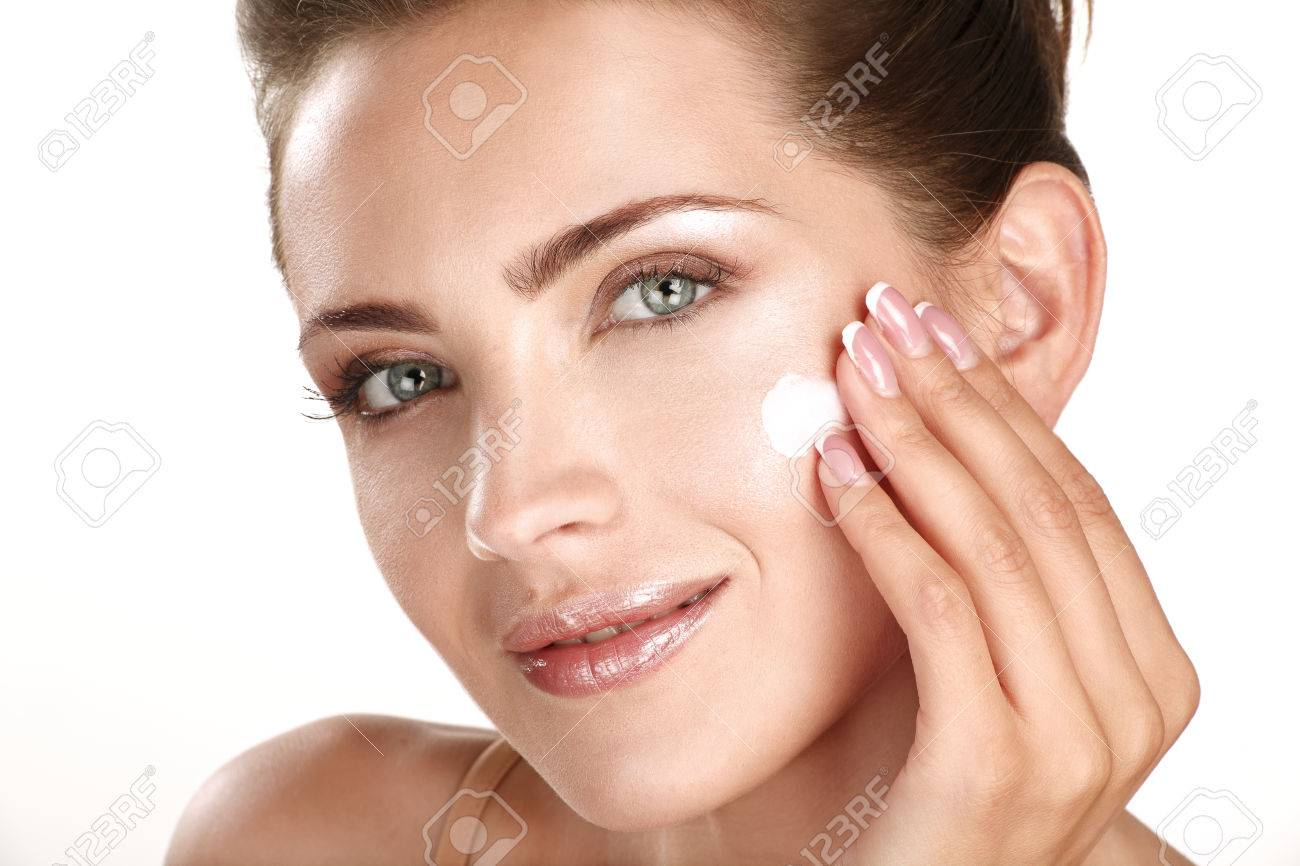 beautiful model applying cosmetic cream treatmen on her face on white - 22642269