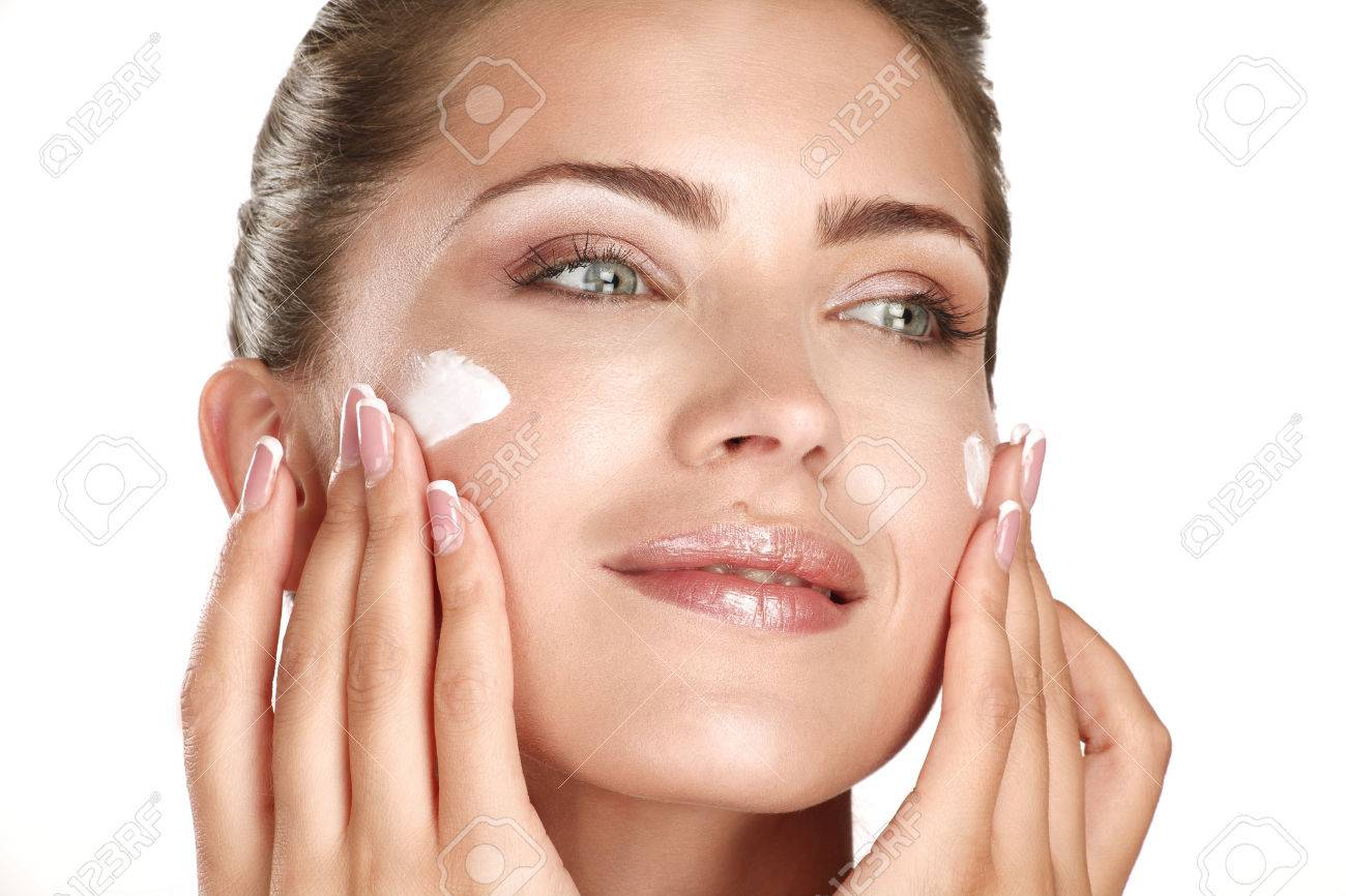 beautiful model applying cosmetic cream treatmen on her face on white - 22642312