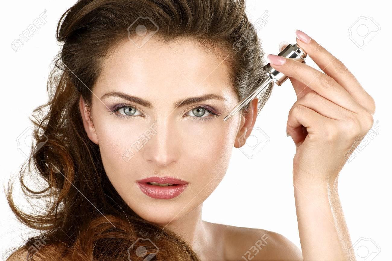 Closeup of a beautiful woman applying a beauty treatment on white - 25391453