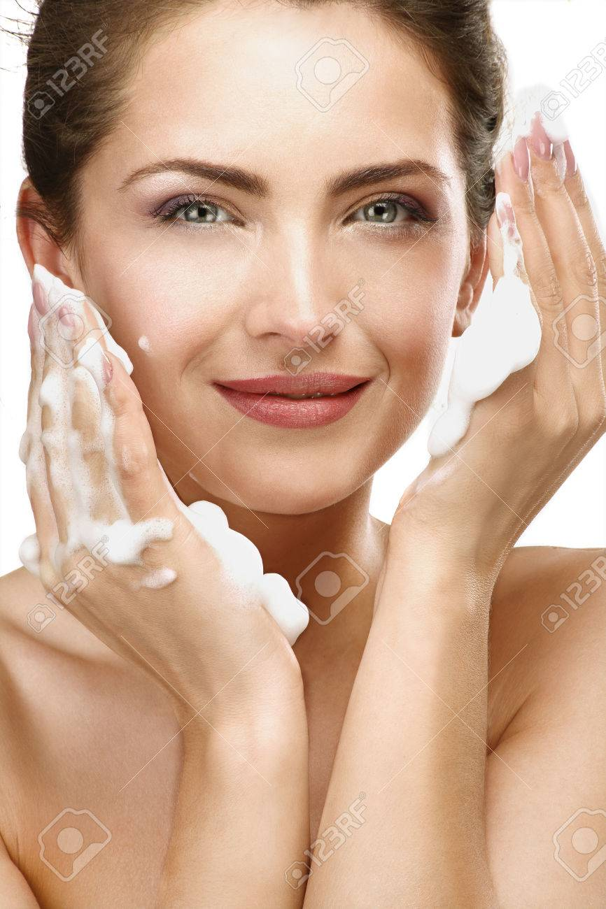 Beautiful woman cleaning her face with a foam treatment on white - 25391462