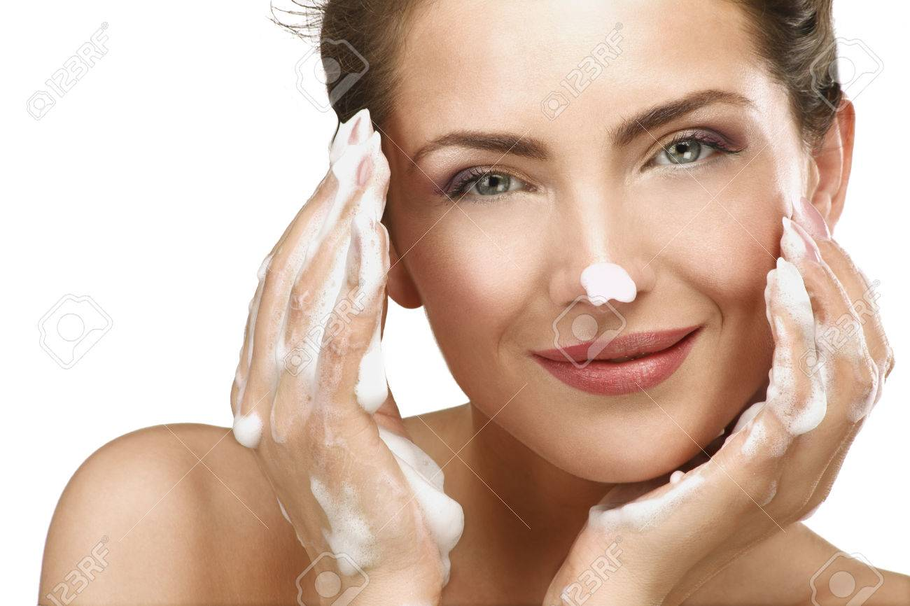 Beautiful woman cleaning her face with a foam treatment on white - 25391472