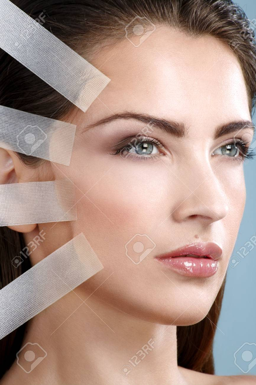 Beautiful woman applying tape lifting treatment on face on blue wall - 26170436