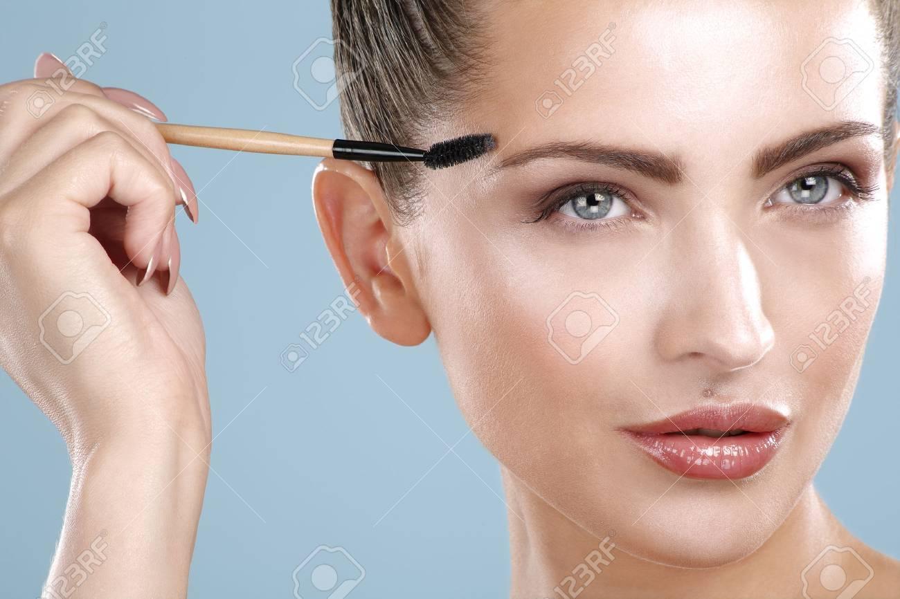 Closeup beautiful woman with eyebrow brush tool on blue - 26159410