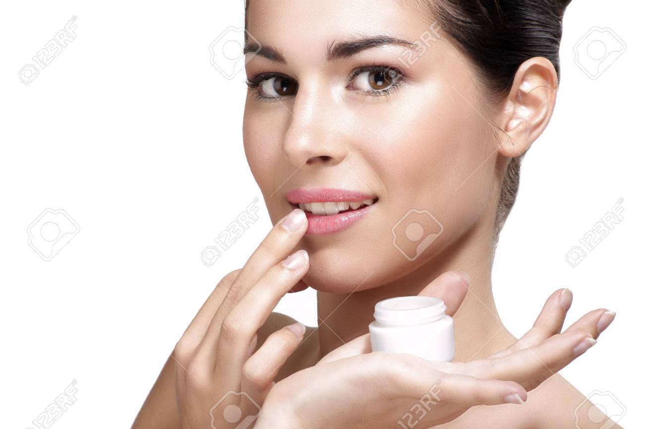 Young beautiful woman applying cream treatment on skin white background - 32886988