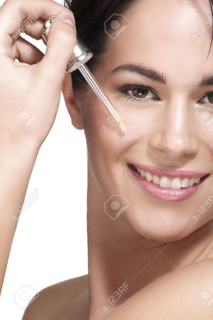 beautiful model applying a skin serum treatment on white - 32887031