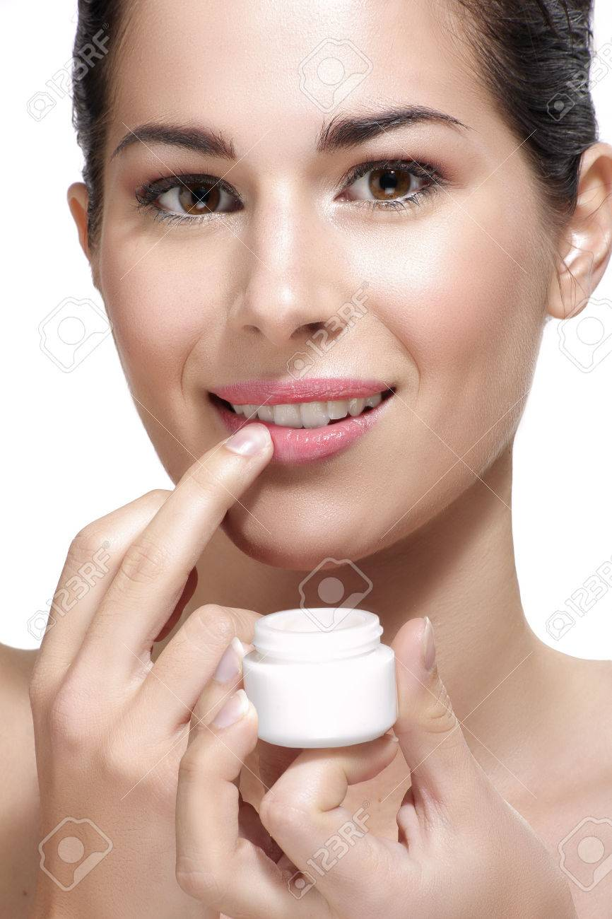 Young beautiful woman applying cream treatment on skin white background - 32887040