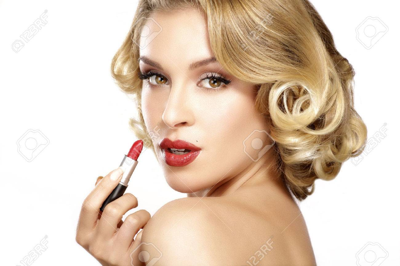 Beautiful young blond model curly hair applying lipstick on white - 36913065